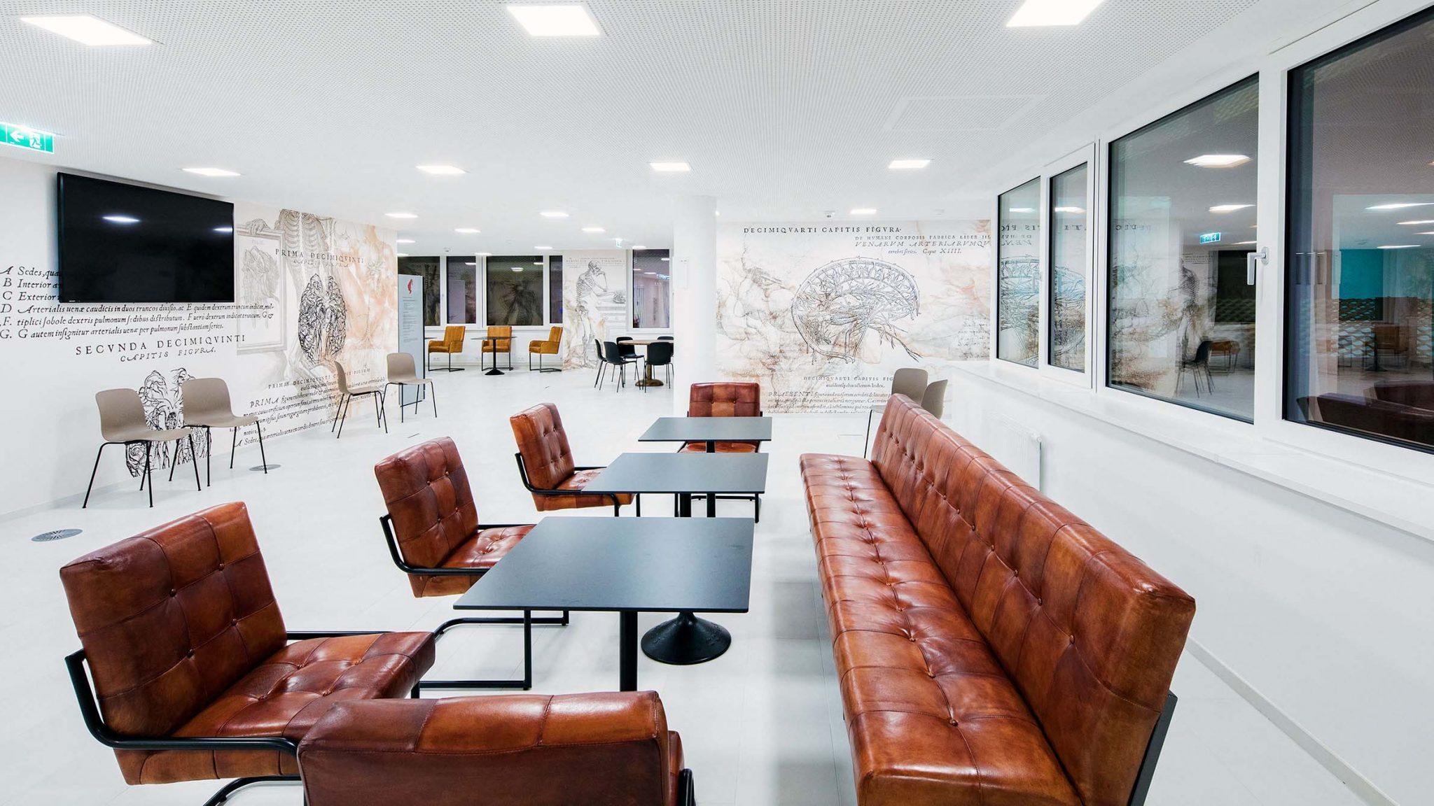 Aufnahme des Sitzbereiches eingerichtet mit Tischen, Stühlen und langem Ledersofa, thematische Tapeten mit anatomischen Motiven.
