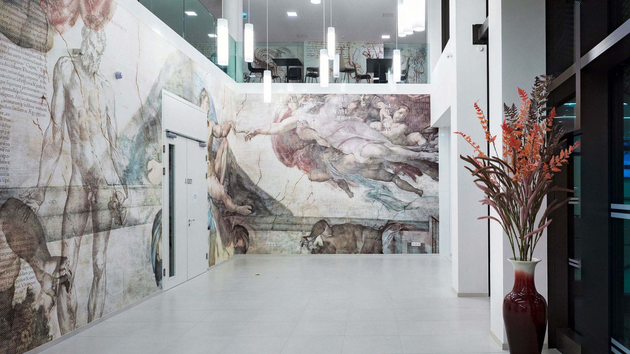 """Foyer der SFU mit Tapete mit neu interpretiertem Motiv """"Die Erschaffung Adams"""" von Michelangelo."""