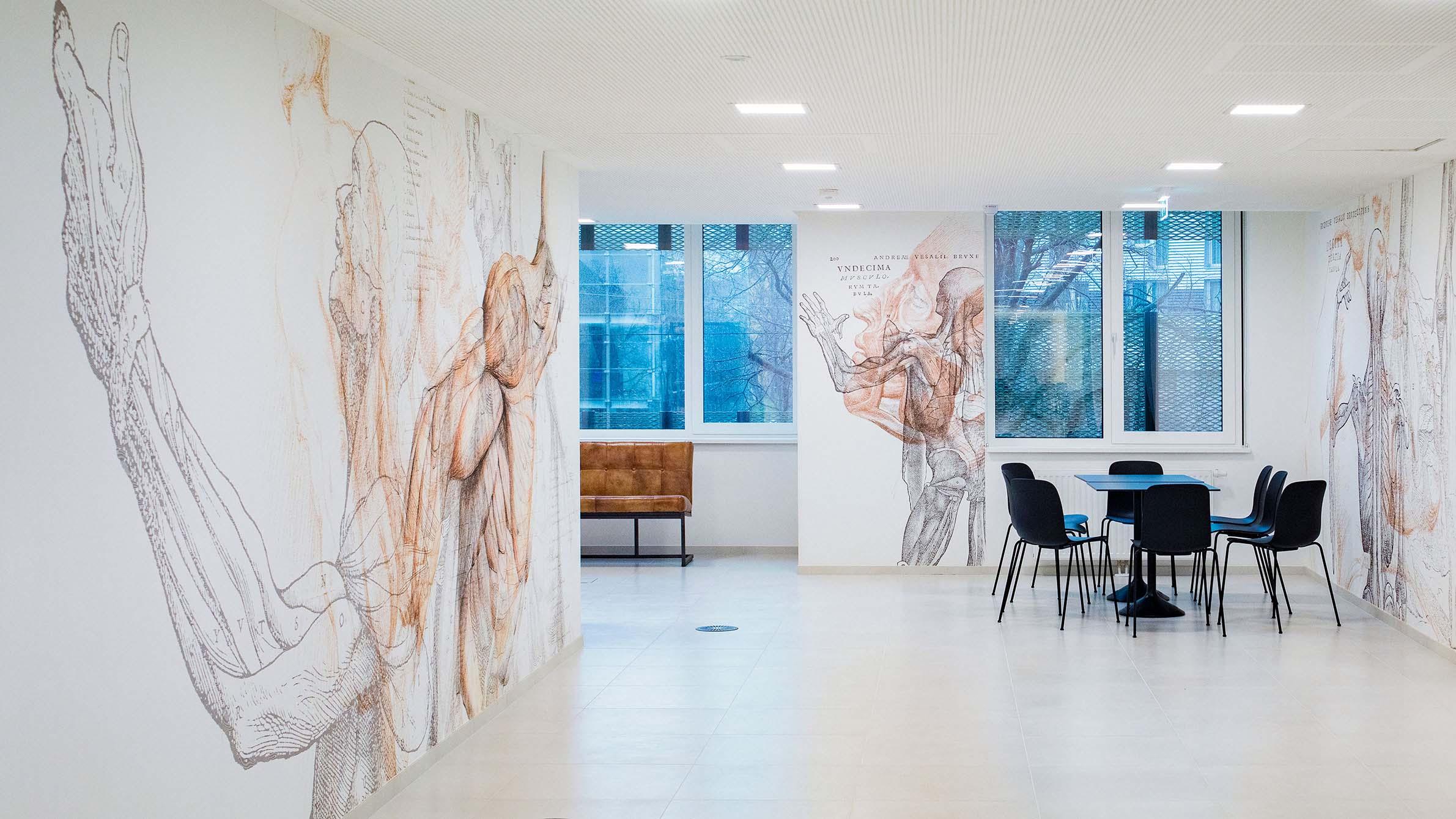 Kleiner Bereich mit Sofa, Tisch und Stühlen, mit Wandtapete, die anatomischen Motiven zeigen.