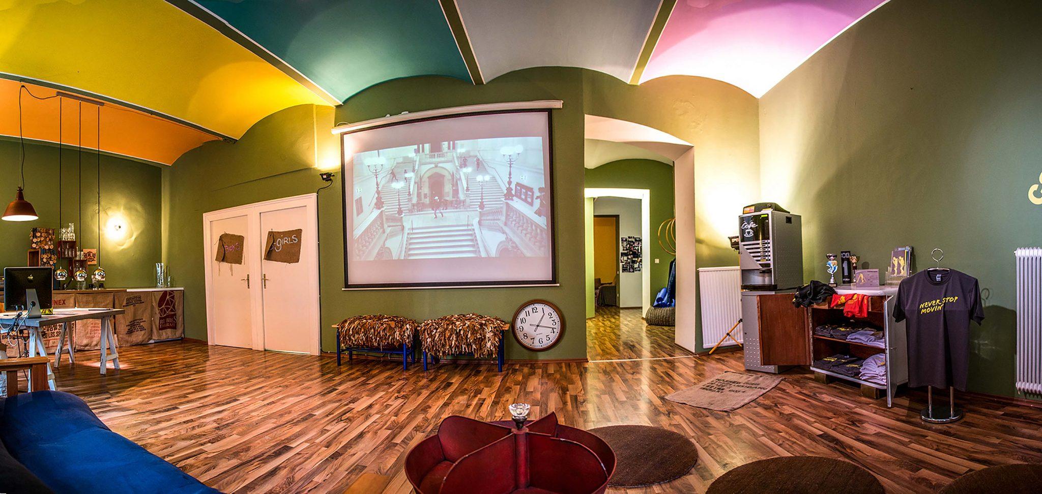 Eingangsbereich mit Farbkonzept, ausgewählten Möbel und Leinwand mit Imagefilm.