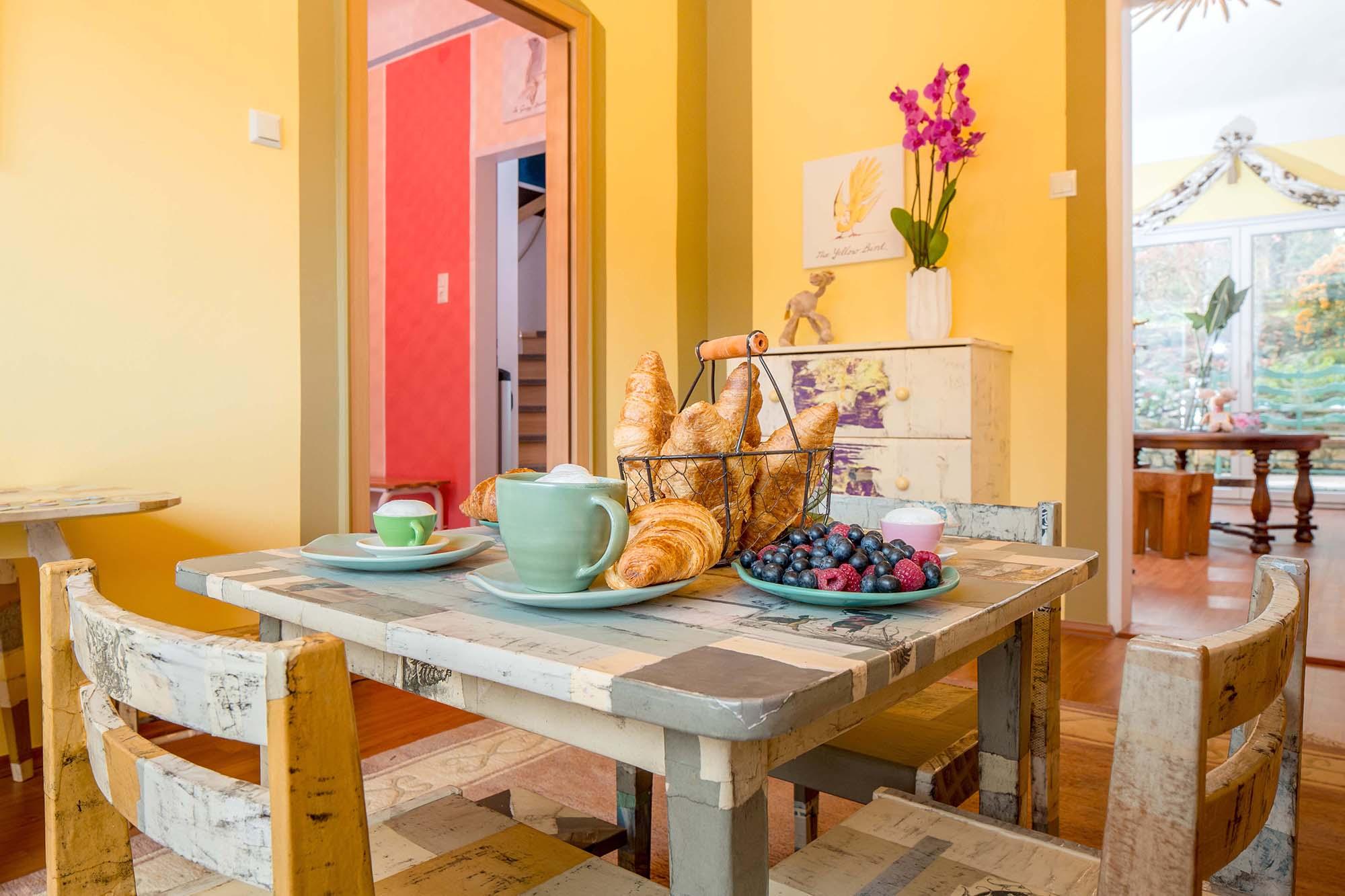 In hellen, sonnigen Tönen ausgemaltes, eingerichtetes Zimmer mit gedecktem Frühstückstisch.