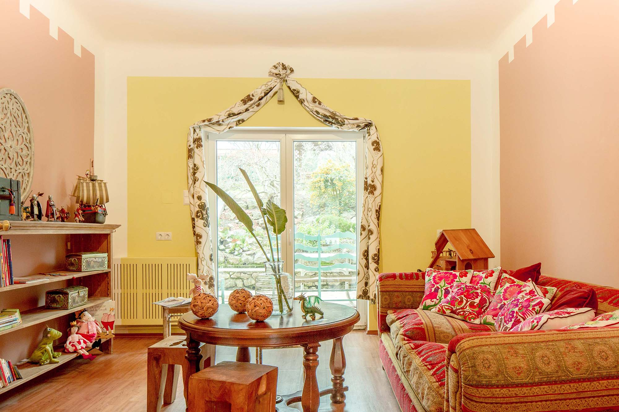 Spielzimmer mit Sofa, Tisch und Regal als Interieur, Ausgang auf die Terrasse.