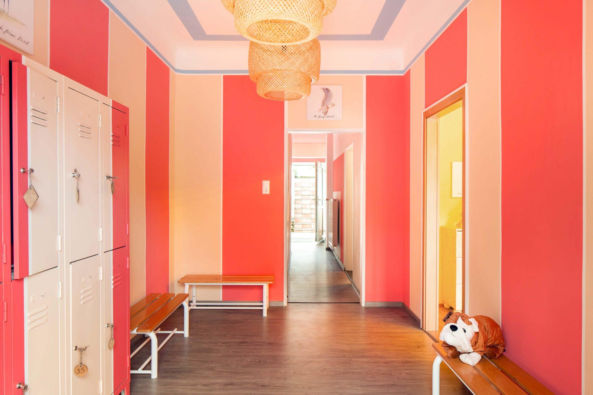 Eingangsbereich mit Garderobe und Wandfarbe in Gelb und Orange.