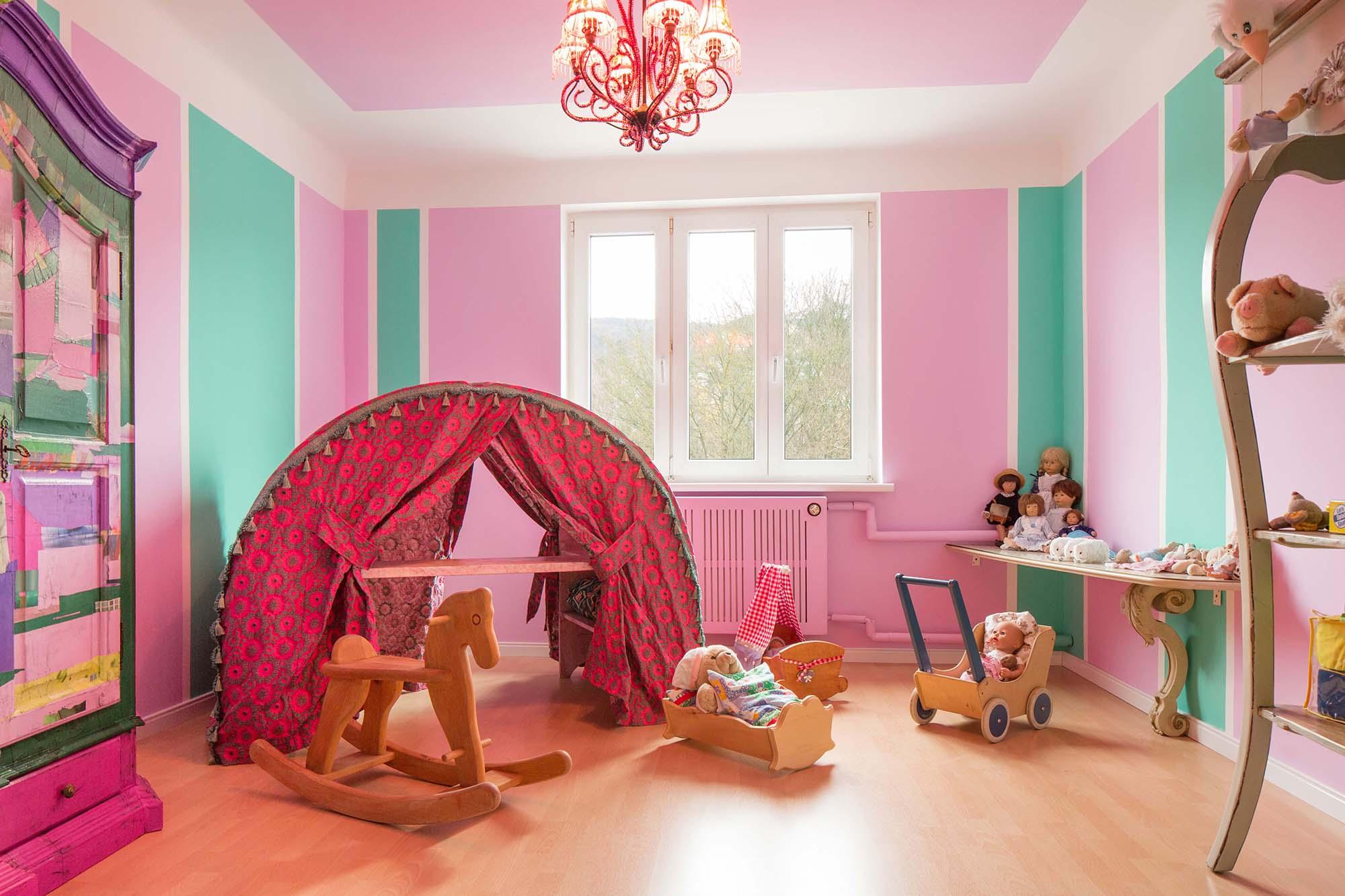 Spielzimmer grün und rosa gestrichen, mit Spielzelt, Schrank und Sideboard als Einrichtung.